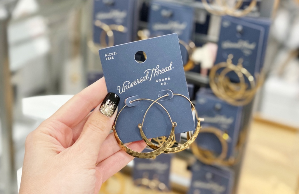 hand holding pair of gold hoop crescent earrings
