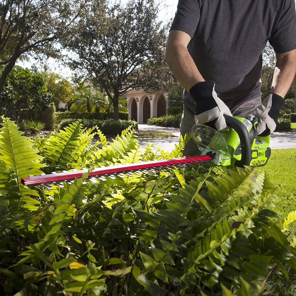 man trimming greenery with Greenworks Trimmer