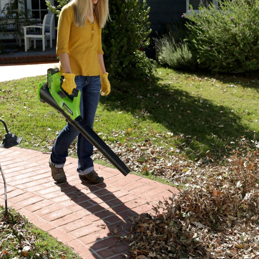 woman clearing leaves with the greenworks leaf blower