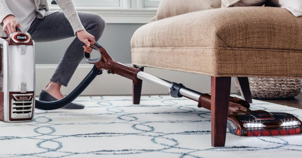 Woman vacuuming under chair with Shark Powered Lift-Away Speed DuoClean Vacuum