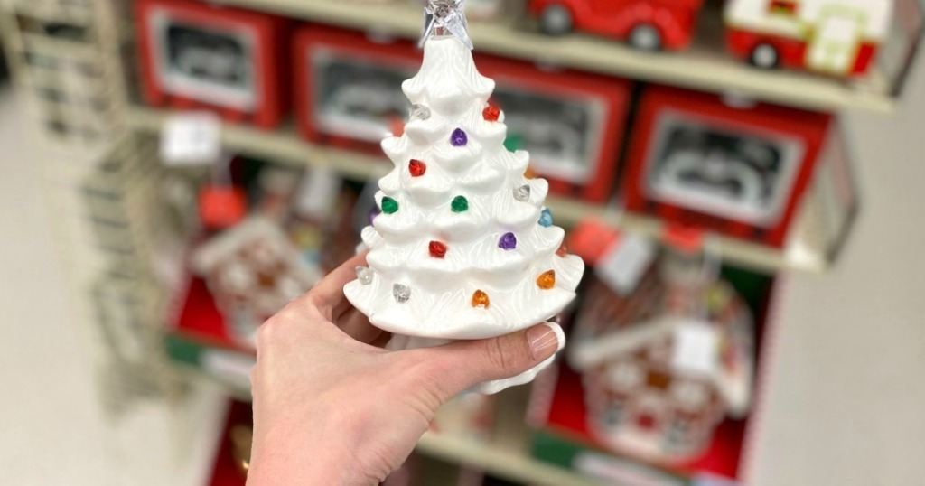 holding small light-up Christmas tree