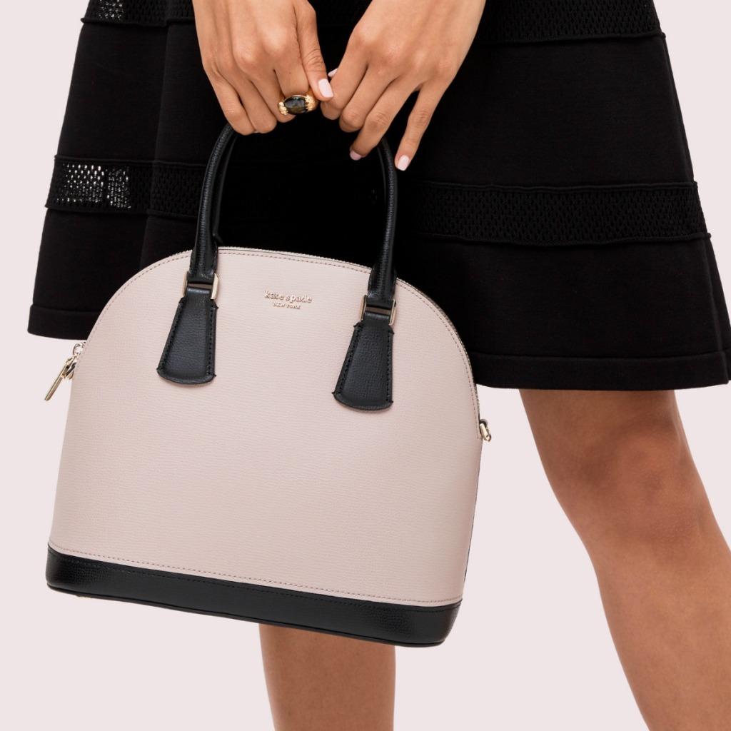 Woman holding kate spade brand satchel in beige and black