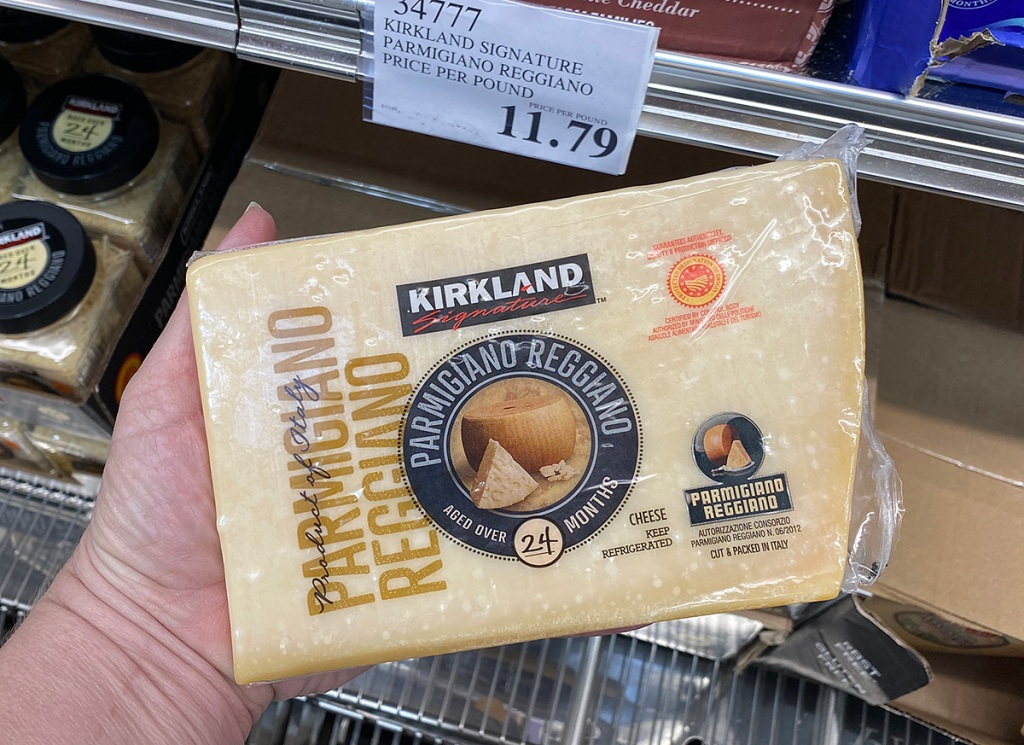 hand holding kirkland cheese at costco