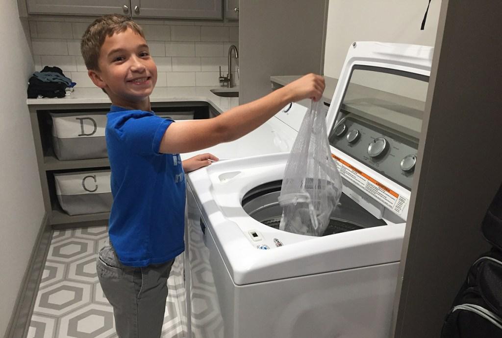 young boy putting mesh bag in washing machine