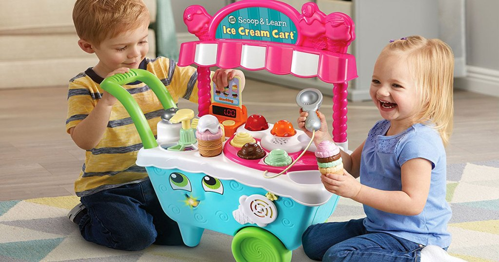 two toddlers playing on the floor with the leapfrog scoop and learn ice cream cart