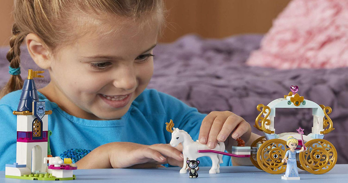 Little girl playing with LEGO Disney Princess Carriage set