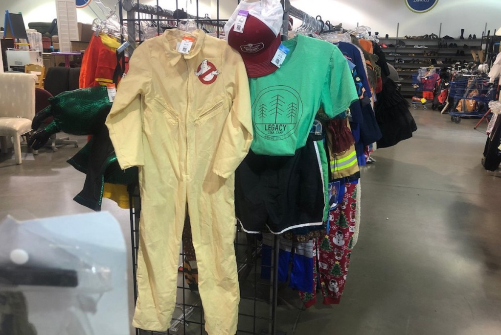 two kids halloween costumes hanging on end of clothing rack at store