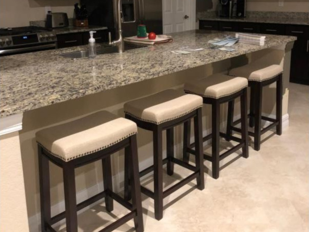 four beige and brown nail head stools in kitchen