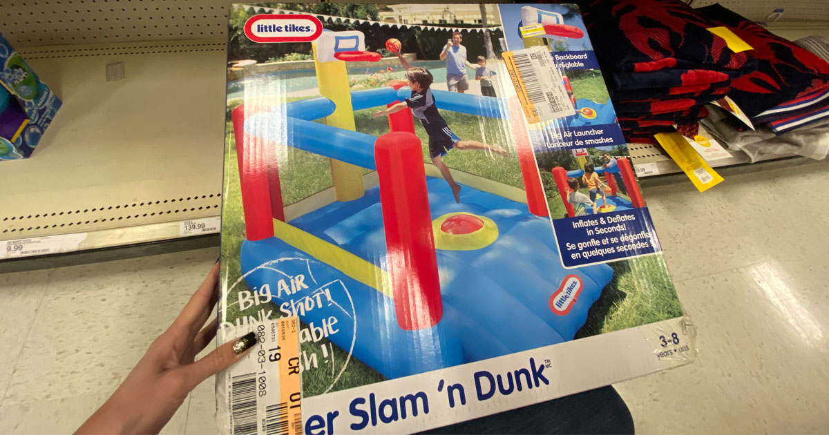 in store picture with hand holding a little tikes slam n dunk bounce house