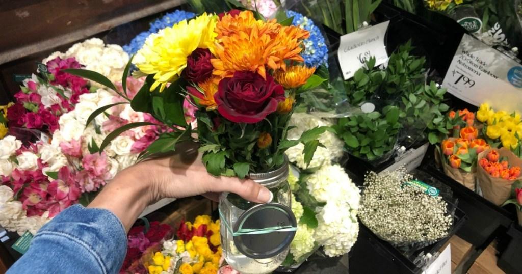 hand holding mason jar full of flowers