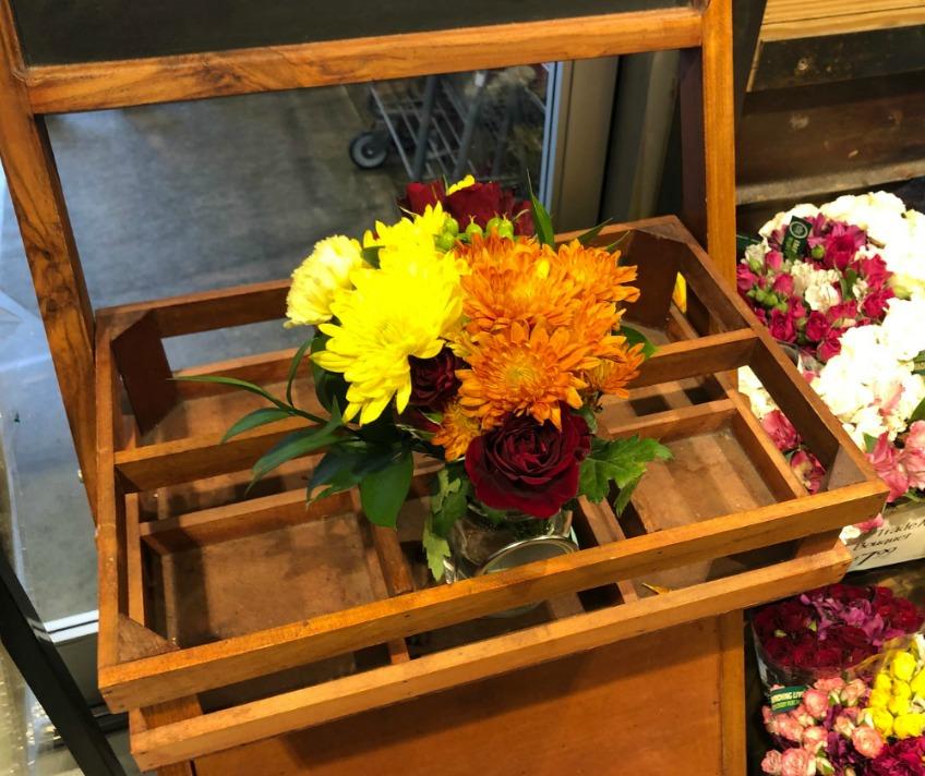 mason jar of flowers on wooden cart