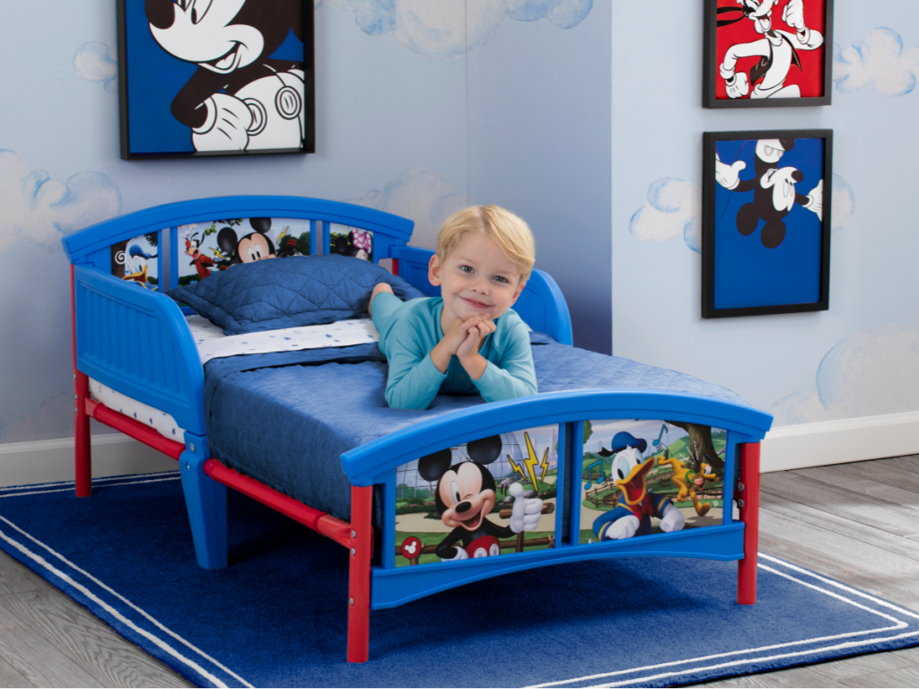mickey mouse toddler bed w/ little boy laying on it