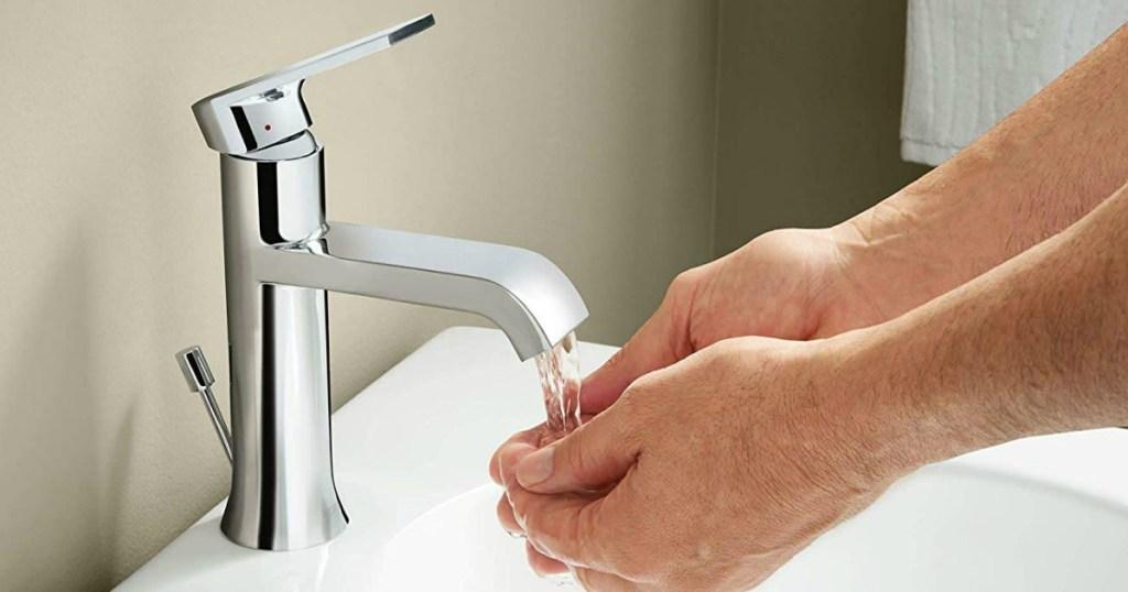 pair of hands washing under water in bathroom sink