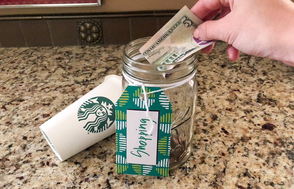 putting $5 bill into money jar next to Starbucks cup