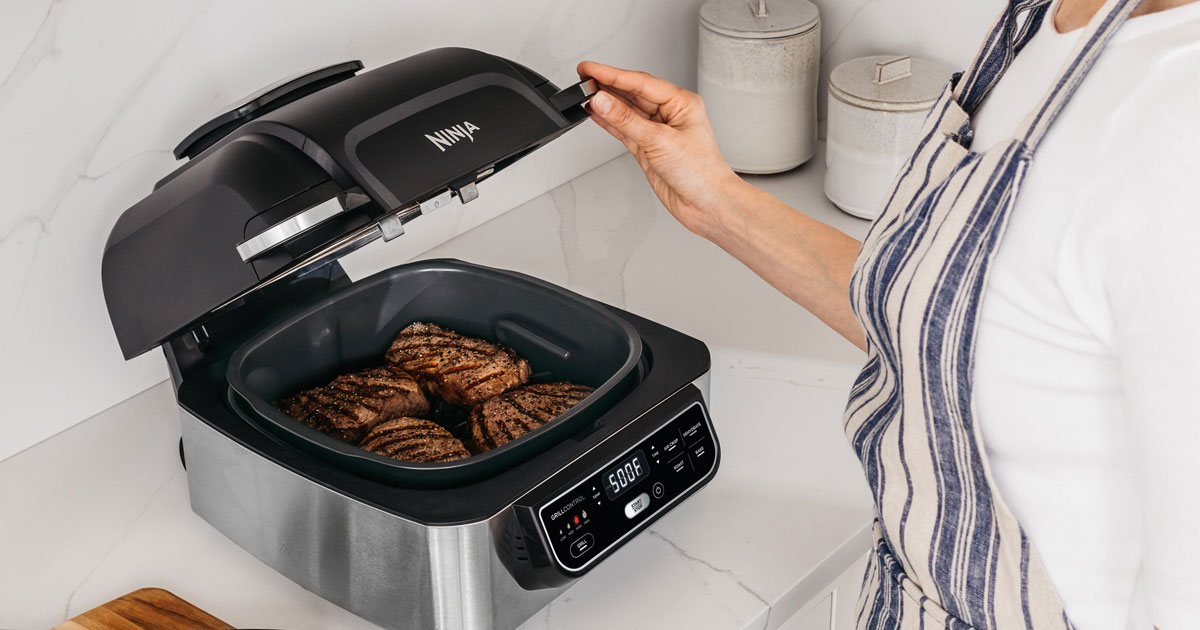 woman standing next to Ninja Foodie 5-in-1 grill