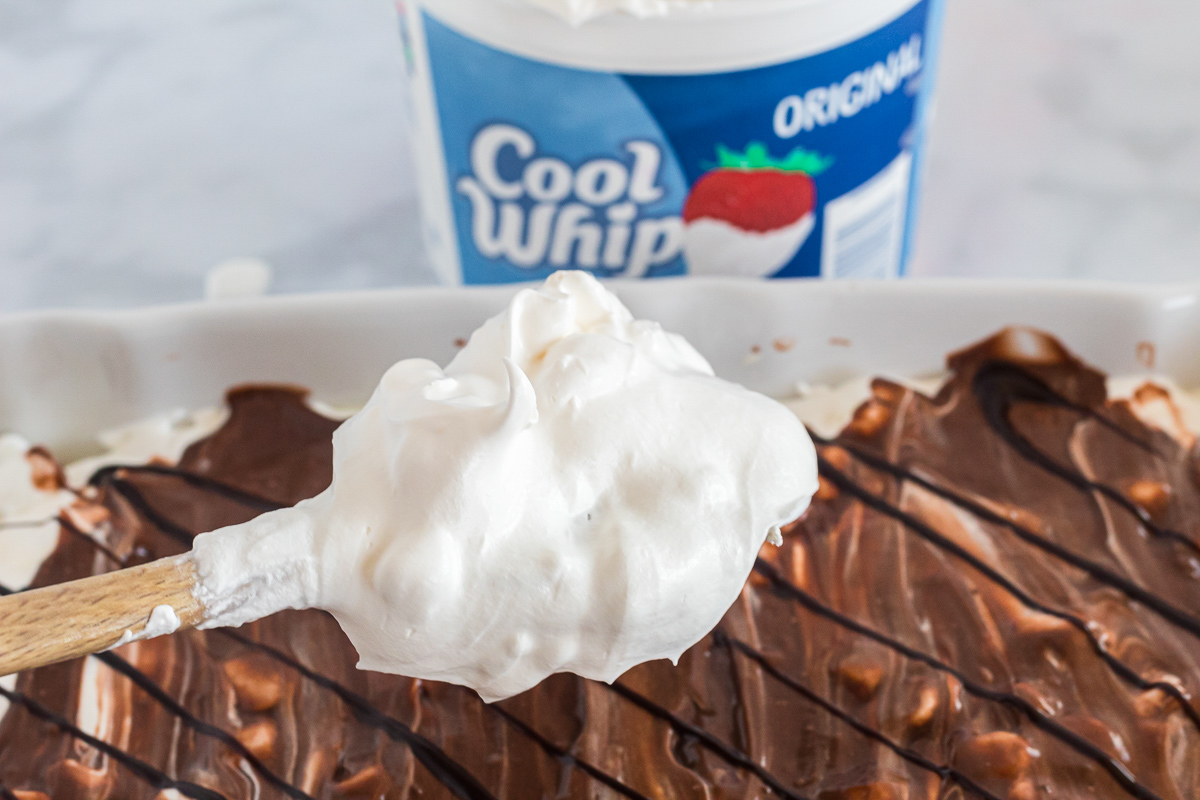 adding cool whip to the top of smores lasagna with spoon