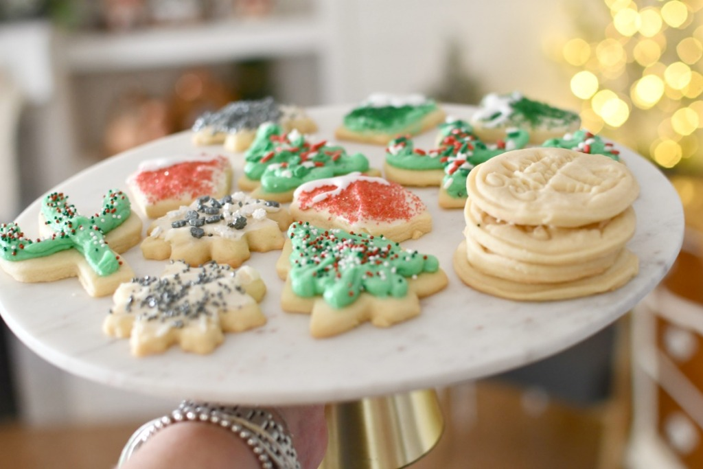 plate of sugar cookies in front of christmas tree