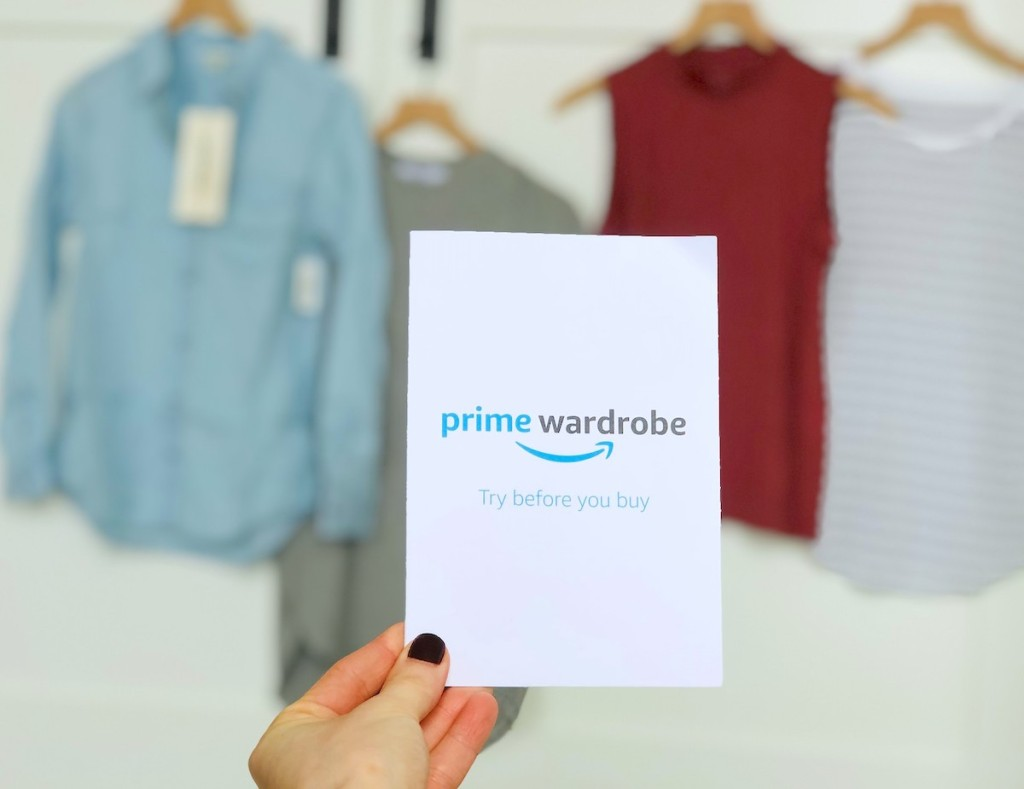 hand holding a prime wardrobe white card with clothes hanging up in the background