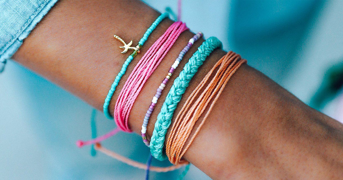 womans wrist wrapped with several bracelets