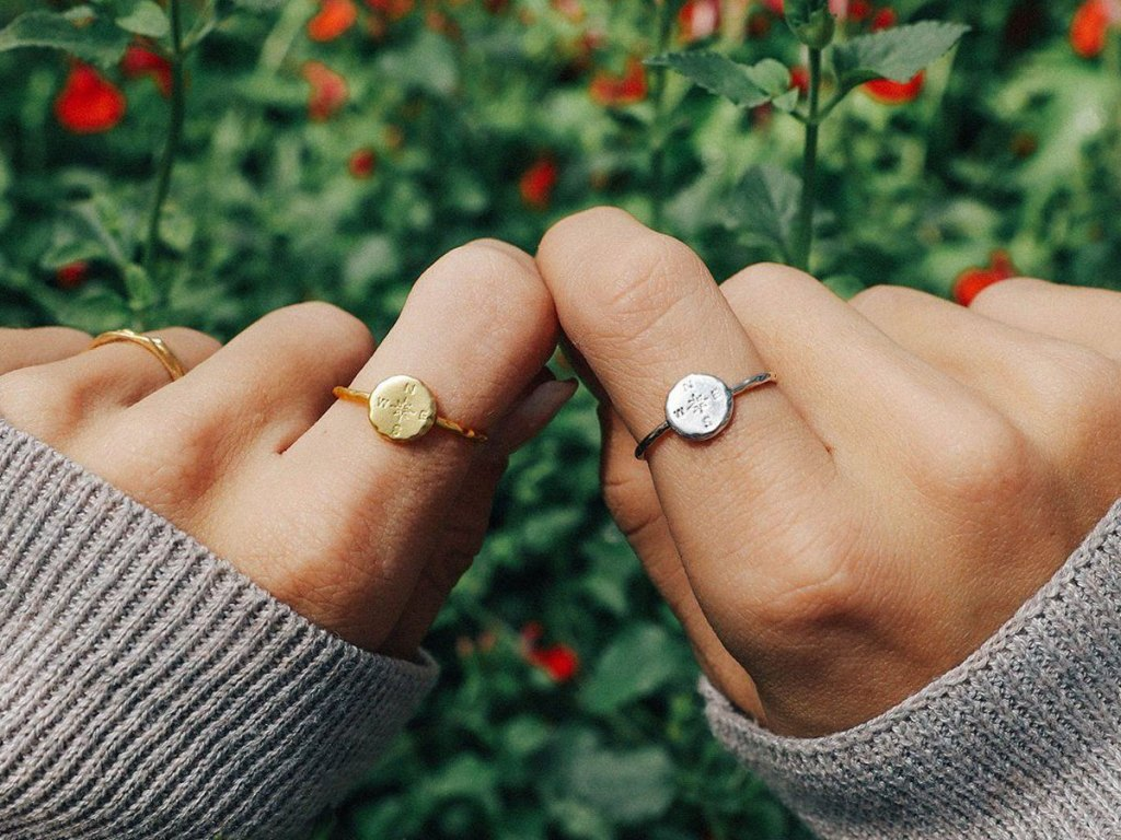 close up of hands wearing puravida compass ring in silver and gold
