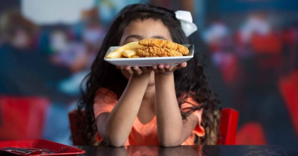 girl holding plate of red robin chicken tender kids meal