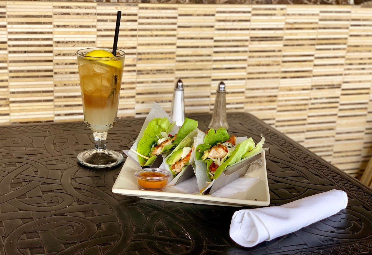 three salad tacos on plate with glass of iced tea