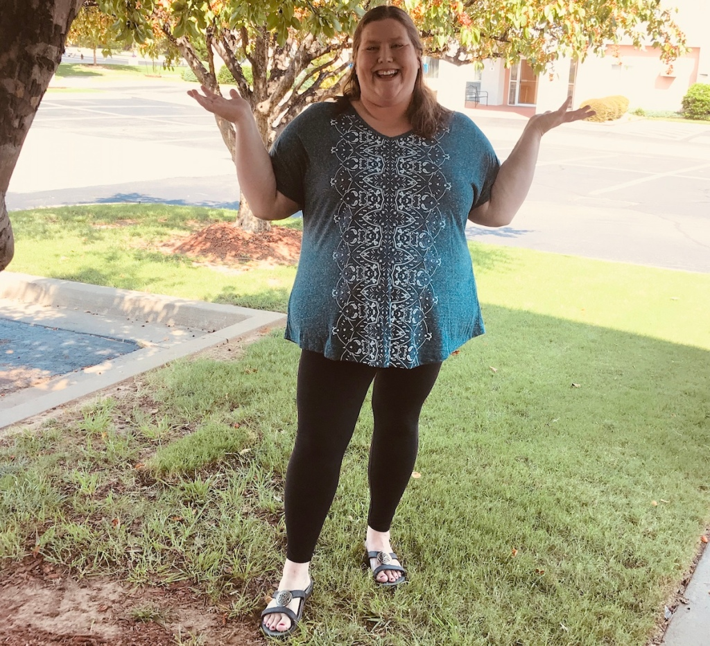 woman wearing black leggings and floral shirt with sandals