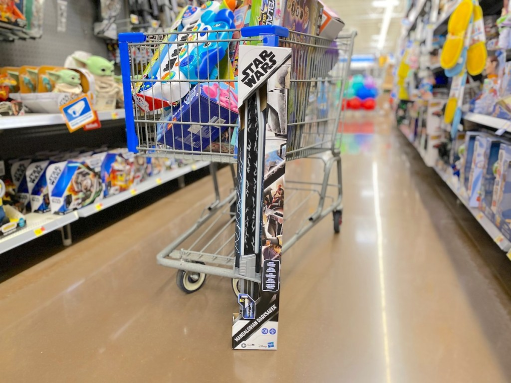 star wars lightsaber sitting on floor leaning on store cart from walmart christmas toy list