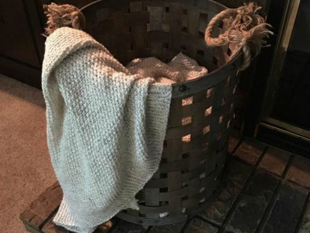 blanket laying over bucket by fireplace