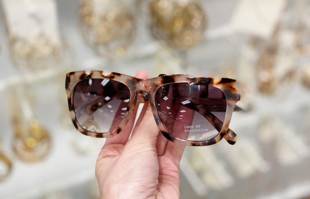 hand holding tortoiseshell sunglasses