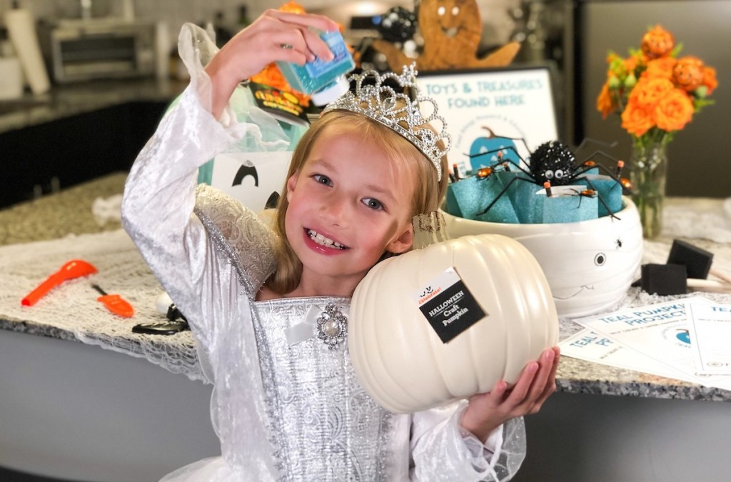girl holding white pumpkin and blue glitter