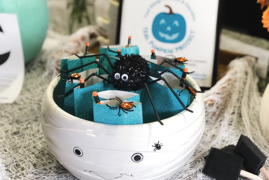 white pumpkin bowl with blue teal goodies inside