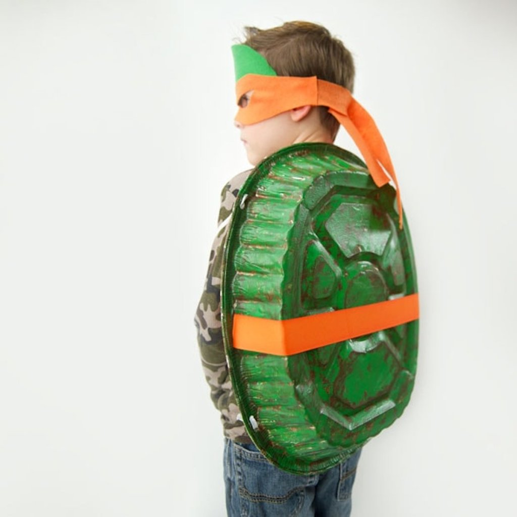 boy wearing orange ninja turtle costume