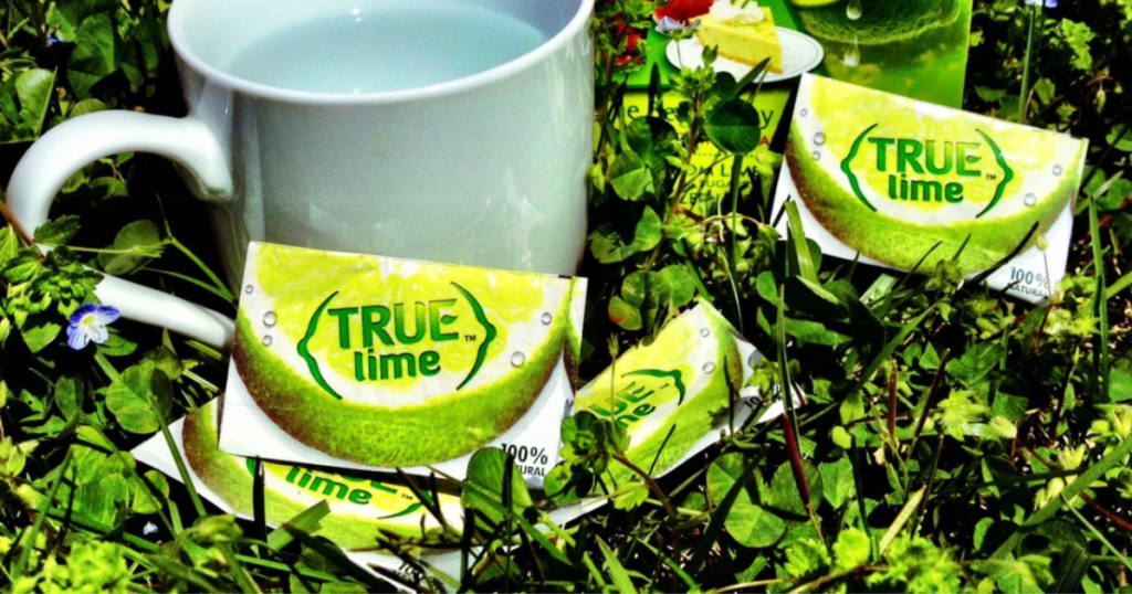 true lime packets on grass with glass of water
