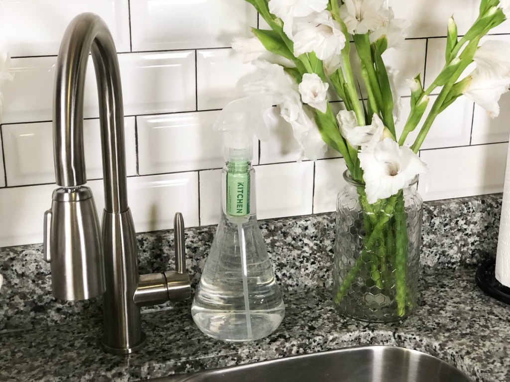 kitchen sink with flowers and cleaners by it