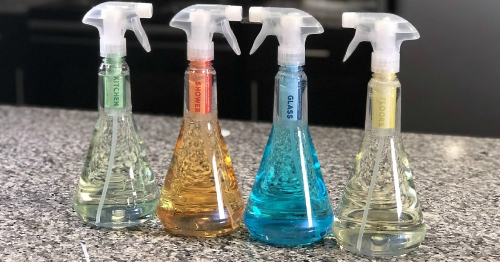 four plastic bottles in different colors on kitchen counter