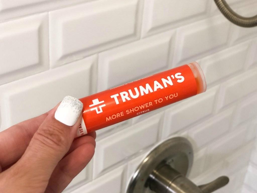 hand holding orange bottle in bathroom