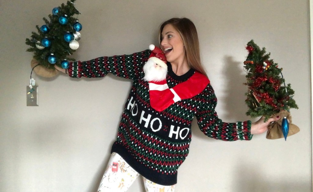 sara wearing ugly christmas sweater holding mini christmas trees
