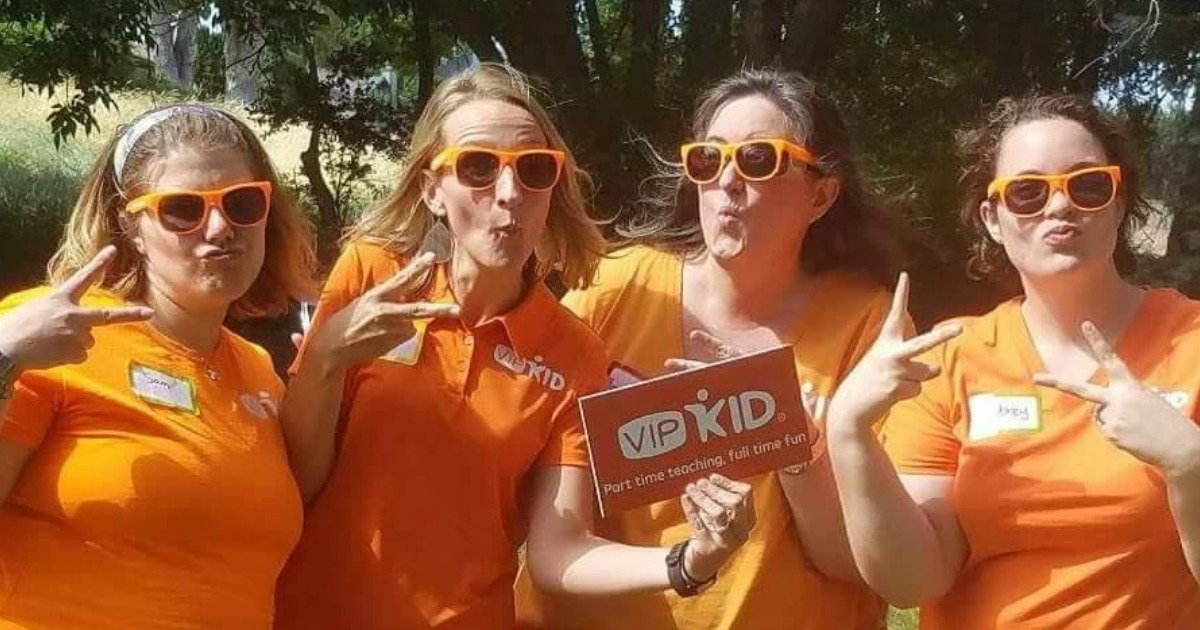 four women standing in orange shirts holding a sign in the park