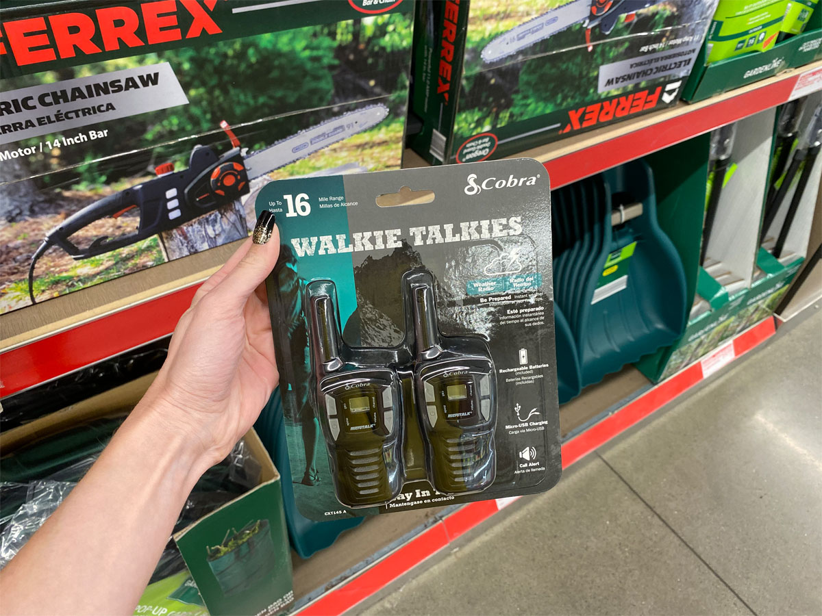 cobra 2 pack of walkie talkies being held up in front of shelf at aldi