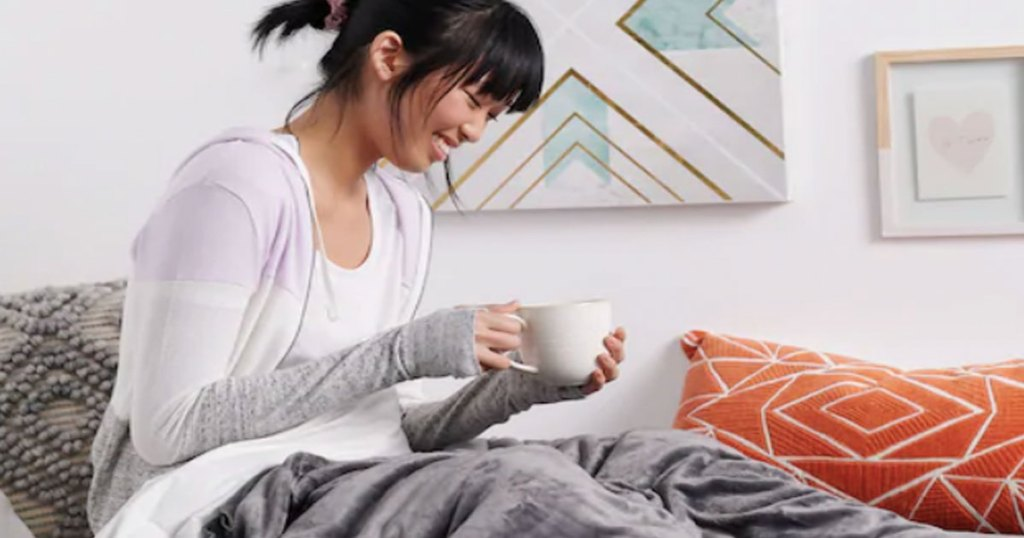 girl laughing drinking tea wrapped in weighted blanket