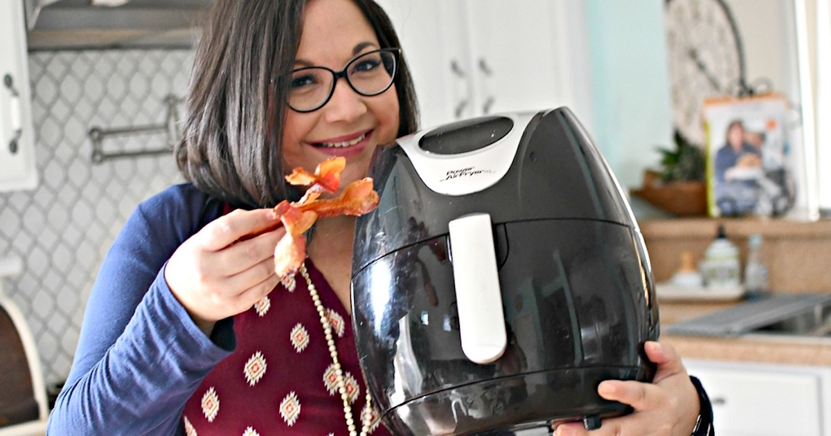 woman holding black best air fryer in one hand and bacon in the other