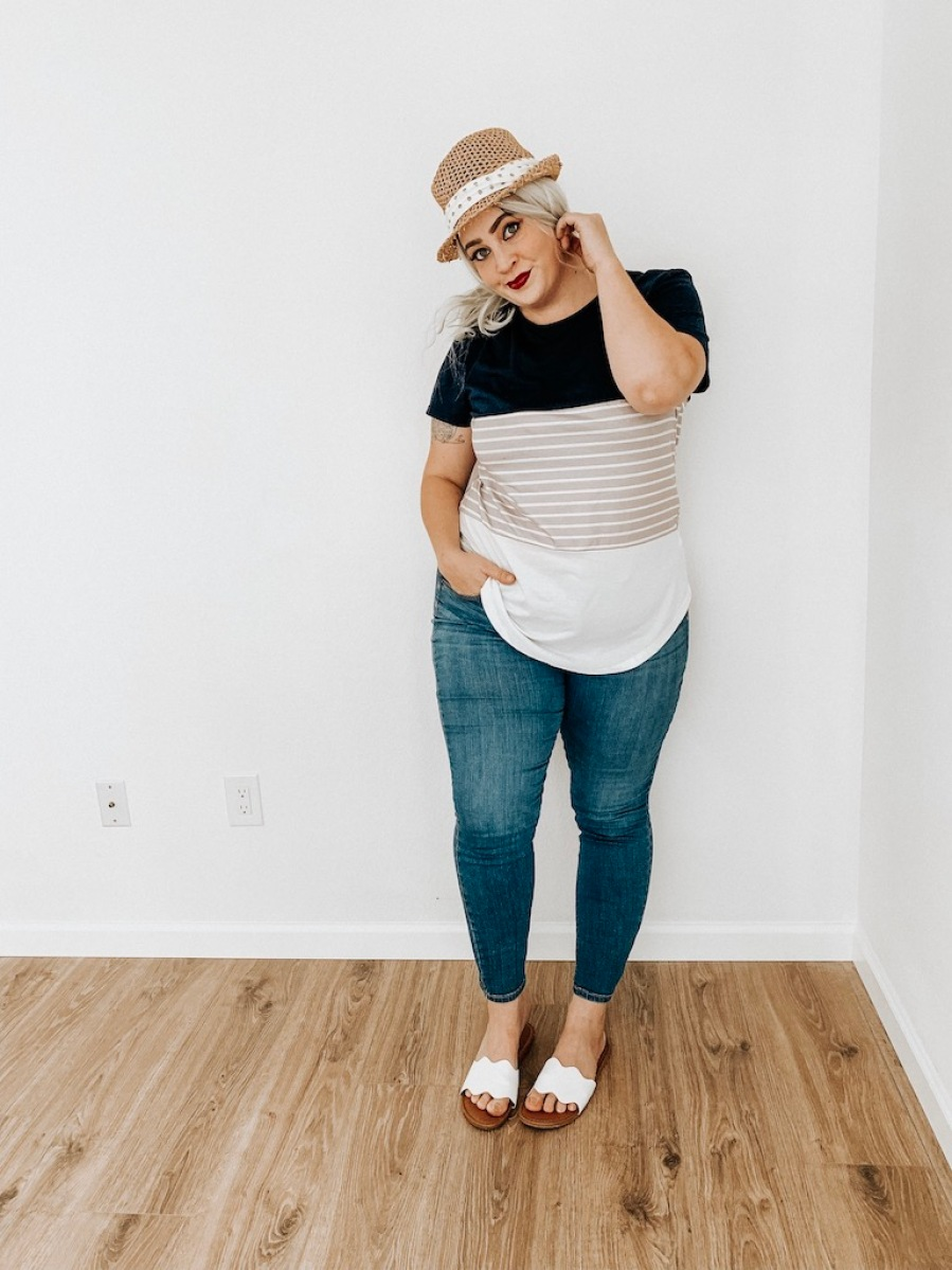 woman wearing fedora hat, striped tee and jeans