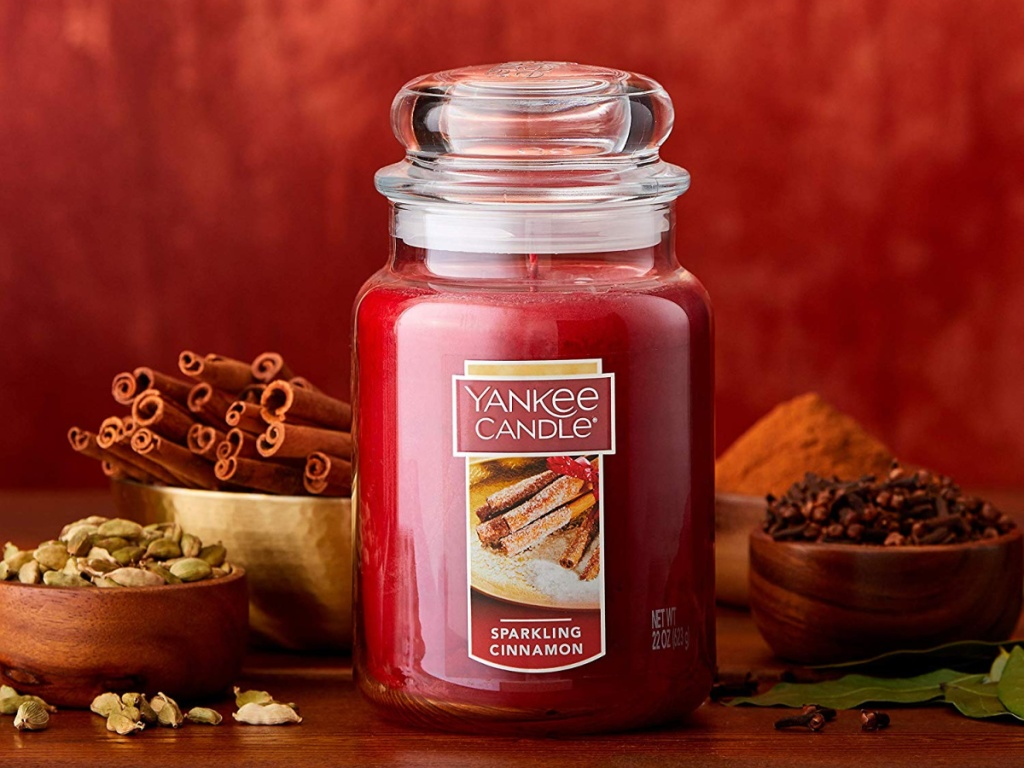yankee candle sparkling cinnamon candle with cinnamon in bowls behind it