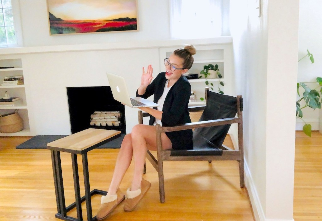 woman waving to laptop sitting in chair