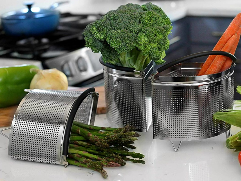 Three steamer basket separates with veggies inside on a counter top