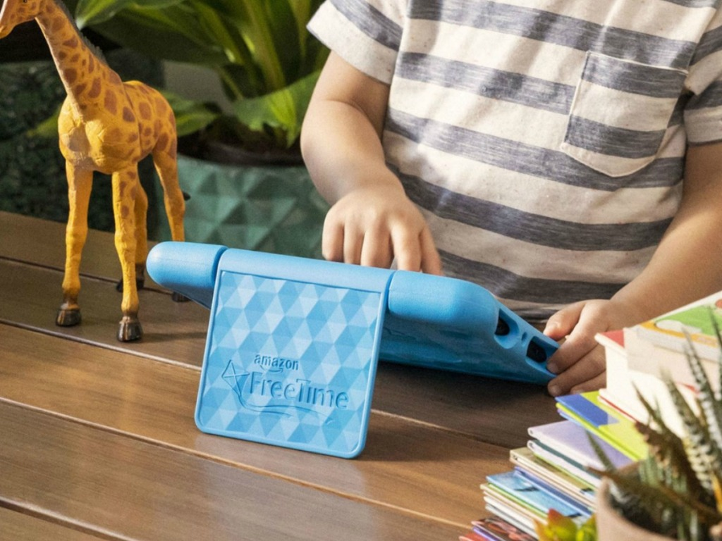 Kid using Fire tablet on table with books and toy giraffe