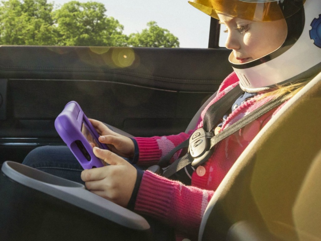 Kid in a carseat using a Amazon Kids Fire Tablet QVC