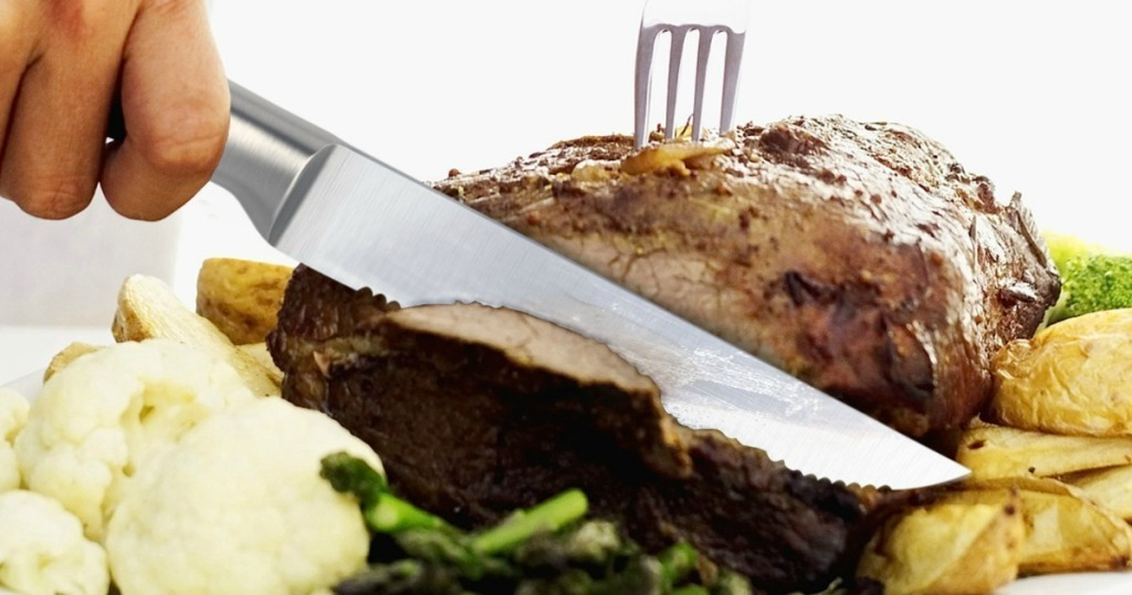 Stainless steel serrated knife cutting into a plated steak