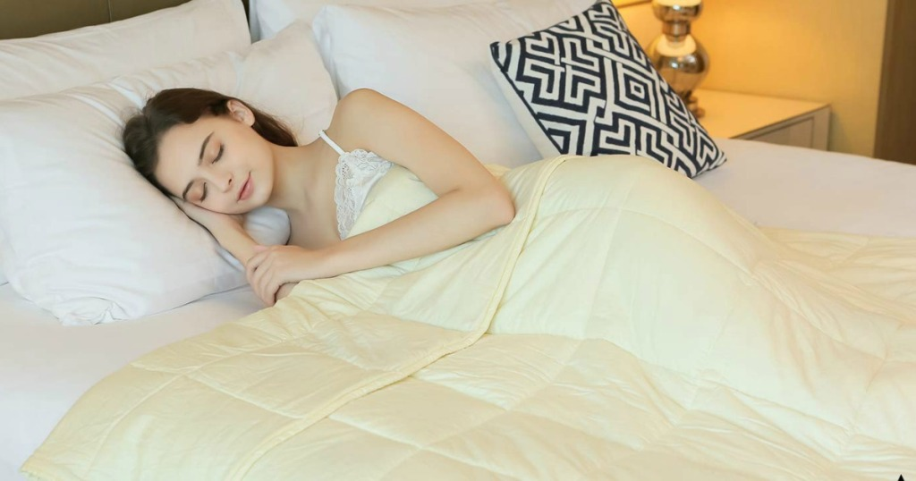 woman laying under weighted blanket